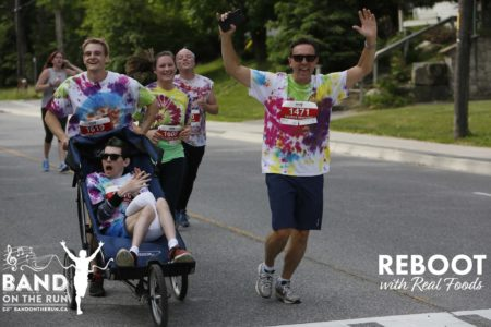 five people in white T-shirts tie-dyed with red, green, blue, purple and yellow jog down a paved residential road. One man is sat in a running stroller, a man pushes the stroller from behind, and another man raises his arms in the air and cheers for the camera.