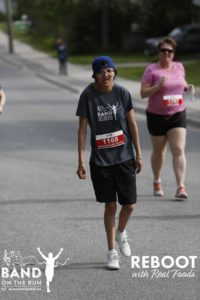 A person in a grey Band on the Run T-Shirt and blue ball cap walks down a paved road. A woman in a pink T-shirt also runs in the background.