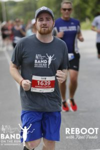 A man in a grey Band on the Run T-shirt, blue shorts and ball cap runs down a paved road. There are more people in the background behind him.