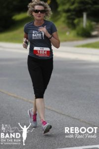 A woman in a grey Band on the Run T-shirt, sport pants and pink-laced running shoes runs down a paved road.