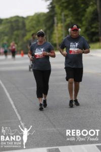 Two people in matching grey Band on the Run T-shirts jog down a paved road.