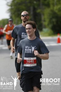 A smiling man with headphones in his ears runs down a paved road. There is a man running behind him in a matching grey T-shirt.