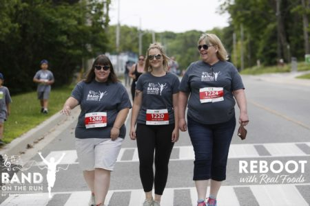 Three women in matching grey T-shirts with race bib numbers pinned to their shirts smile while walking side by side along the race route.