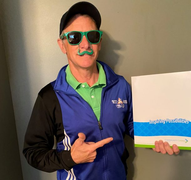 Image shows a man in a green shirt, blue jacket, and green sunglasses with novelty green moustache that dangles over his upper lip. He is holding a folder in one hand and pointing to it with the other. Folder reads: Inspiring possibilities, and includes the Community Living Huntsville logo.