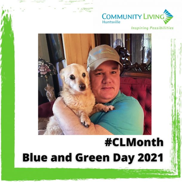 Image shows a man in a green shirt and Community Living ball cap holding a small dog. They are posing for the camera.