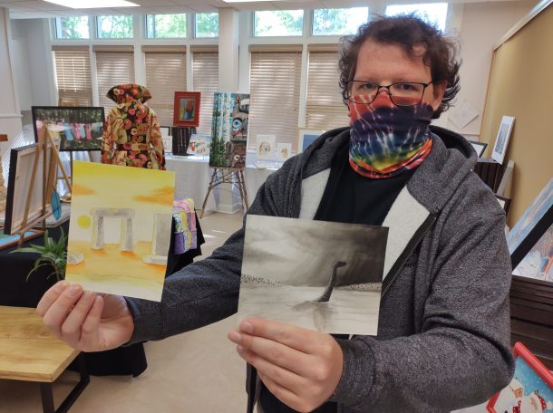 Image shows a man standing in a room filled with art displays. He is wearing a cloth face mask and holding two unframed watercolour paintings. One is yellow and orange in colour, the other is black and white.