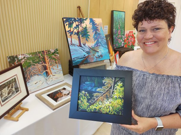 Image shows a smiling woman indoors holding a small framed painting that depicts an outdoor forest and rive scene. There is more artwork in the room behind her.