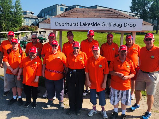Image shows a group of 14 smiling people in matching orange T-shirts and red hats standing outside. A sign behind them reads: Deerhurst Lakeside Golf Bag Drop.