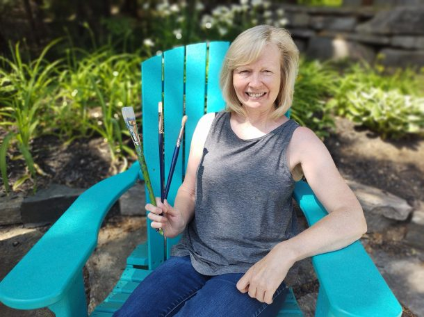Image shows a smiling woman holding three fine art paintbrushes, while sitting in a blue Muskoka chair outside in a garden.