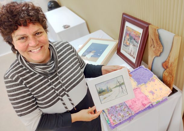 A smiling woman looks up at the camera while holding a small, unframed winter landscape painting. Other art items are on a table beside her, including a colourful fabric lap quilt, a wood and resin sculpture and two other framed pieces of art.