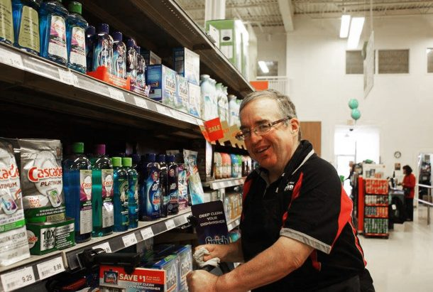 A man in a grocery store aisle smiles at the camera while placing products on the shelf.