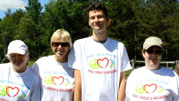 Four people stand together in white T-shirts that read: Peace Love and Inclusion