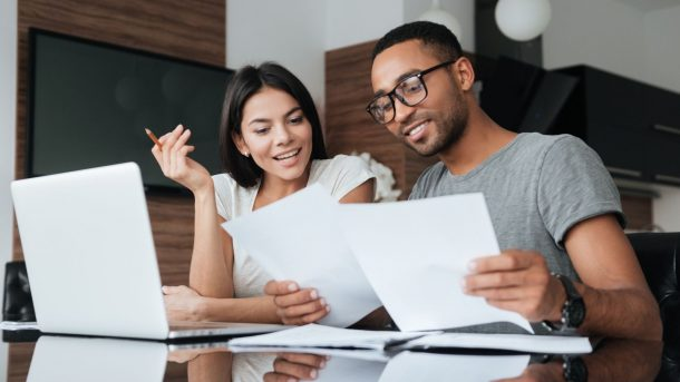 A stock photo of a smiling couple reviewing financial paperwork.
