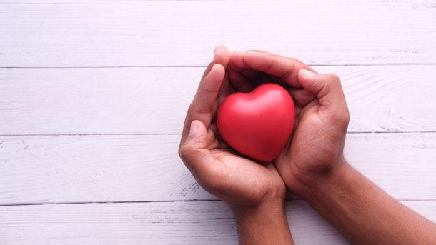 Hands holding a heart-shaped ball