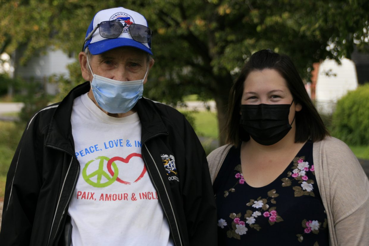 A man and a woman wearing face masks pose for the camera. They are standing near a tree in a park. The man's shirt reads: Peace, Love, and Inclusion. Paix, Amour, and Inclusion.